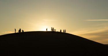 Menschen vor der untergehenden Sonne